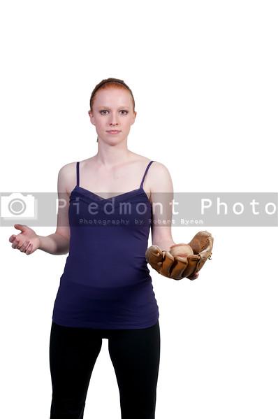 A beautiful woman catchinging a baseball at a ball field