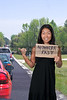 A beautiful young Asian woman holding up a blank sign