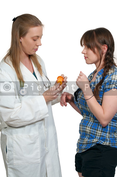 A beautiful young female doctor giving a bottle of prescription pills to a patient