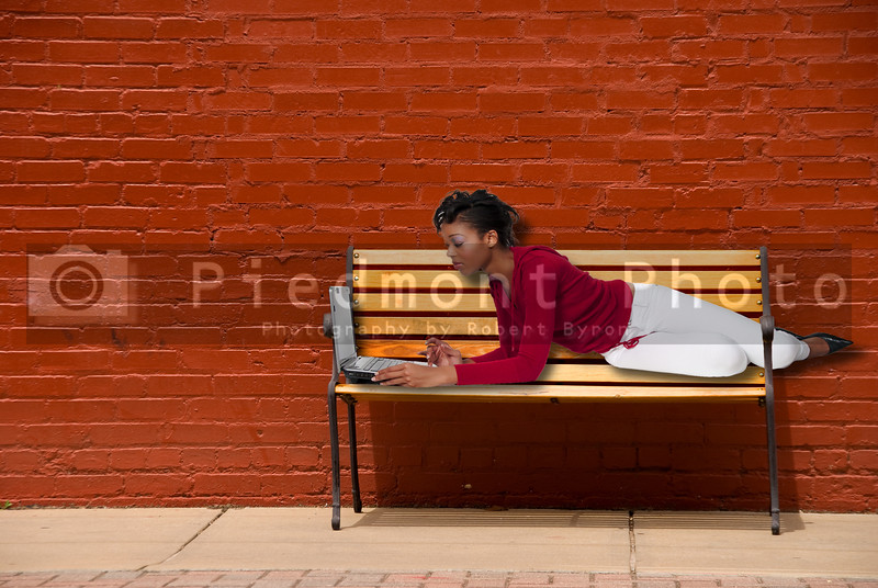 A beautiful black woman college student on a downtown park bench working on a computer