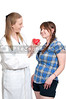 A female cardiologist holding a red heart while talikng to a patient