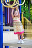 A little girl playing on a jungle gym