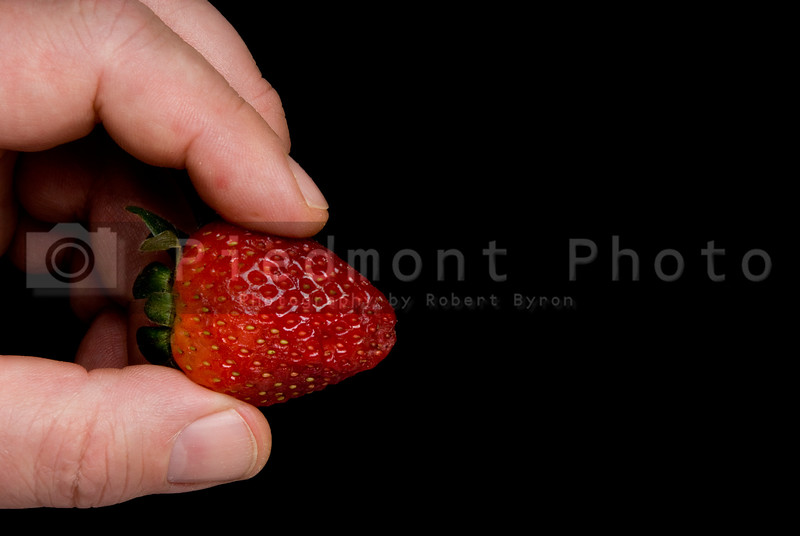 A person holding a sttrawberry between their fingers