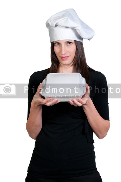 A beautiful young woman chef holding a togo box
