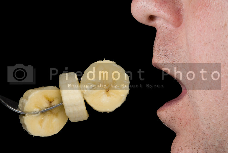 A man eating delicious freshly sliced bananas