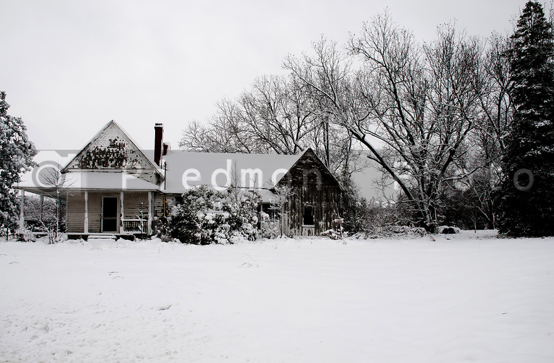 An old abandoned house covered in a winter blizzard snow storm