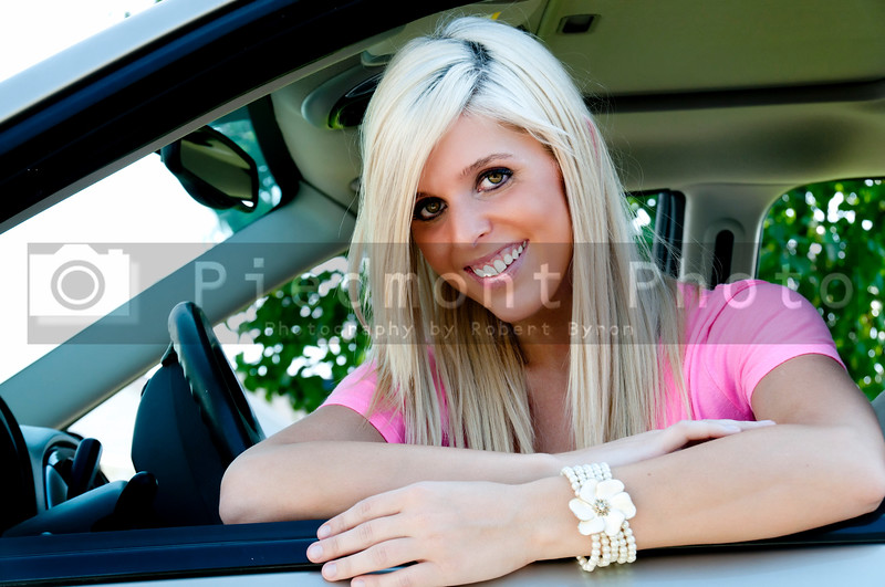 A beautiful young woman sitting in a car