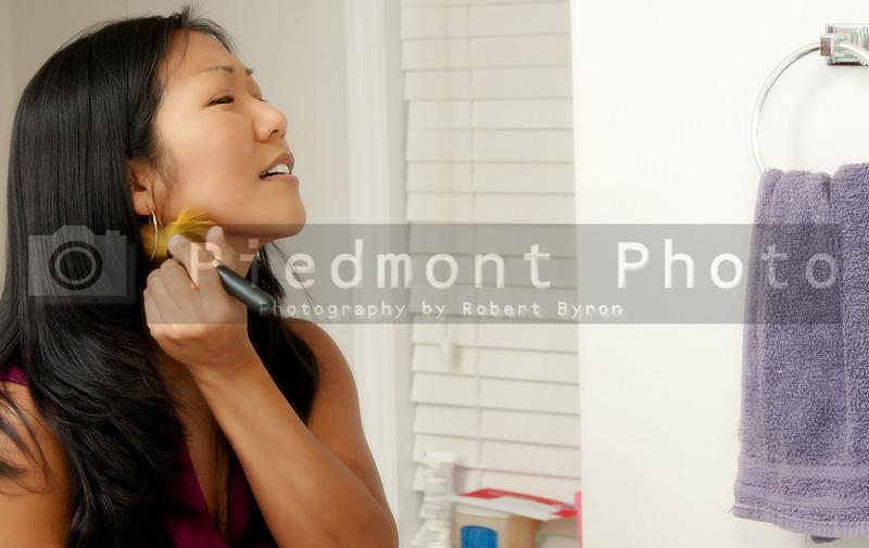 A beautiful young asian woman applying makeup