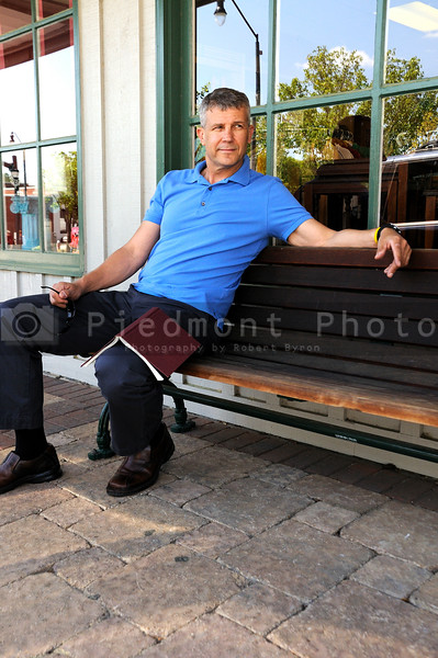 A handsome middle aged man sitting on a bench