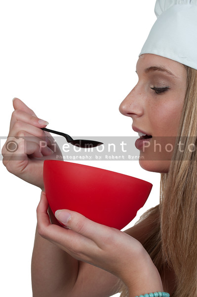 A beautiful woman chef eating food from a bowl