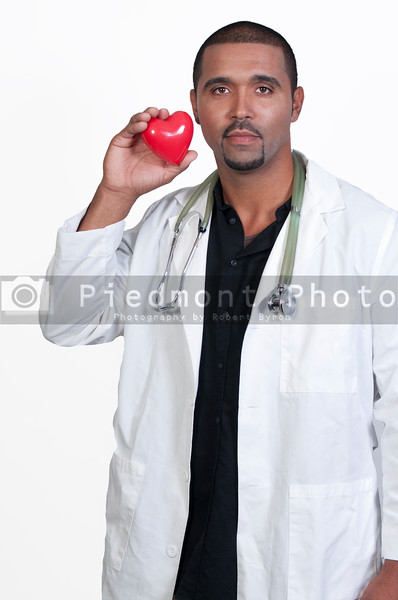 A male cardiologist holding a red heart
