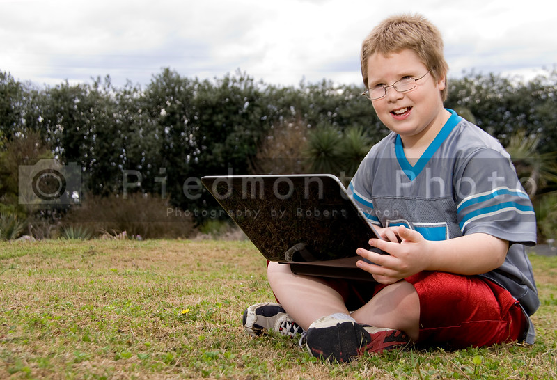 A smiling young boy using a laptop computer