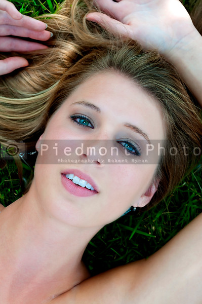 A beautiful young woman laying in a grassy yard