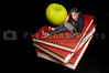Back to School Concept - A teacher or teenager woman sitting beside an apple on a book.