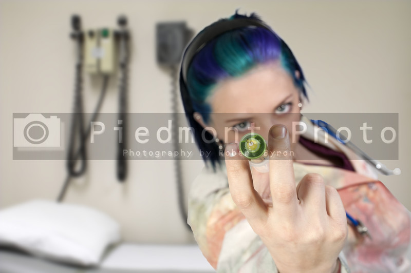 A syringe being held by a blurred doctor