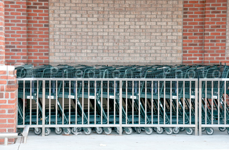 A series of shopping carts at a retail store.