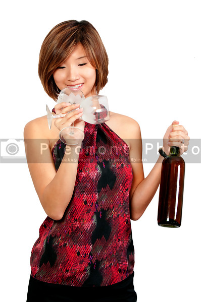 A beautiful Asian woman holding a wine bottle and glasses