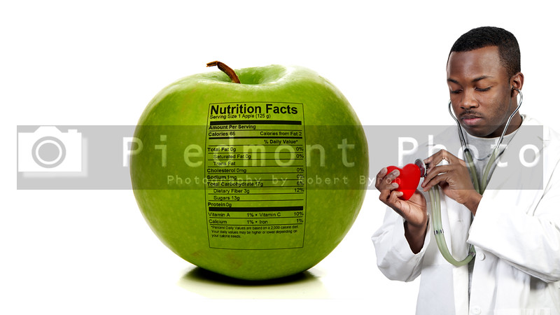 An Apple a Day Keeps the Doctor Away - A black male African American doctor cardiologist holding a red heart standing next to an apple