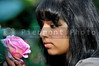 A young Indian woman smelling a flower