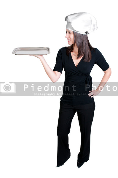 A beautiful young woman chef holding a silver tray