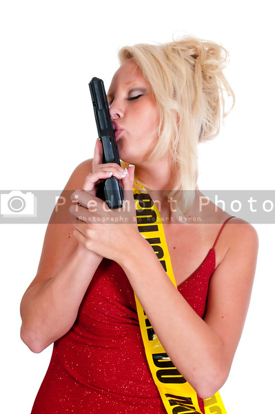 A young and beautiful woman holding and kissing a handgun wearing police line tape as a sash