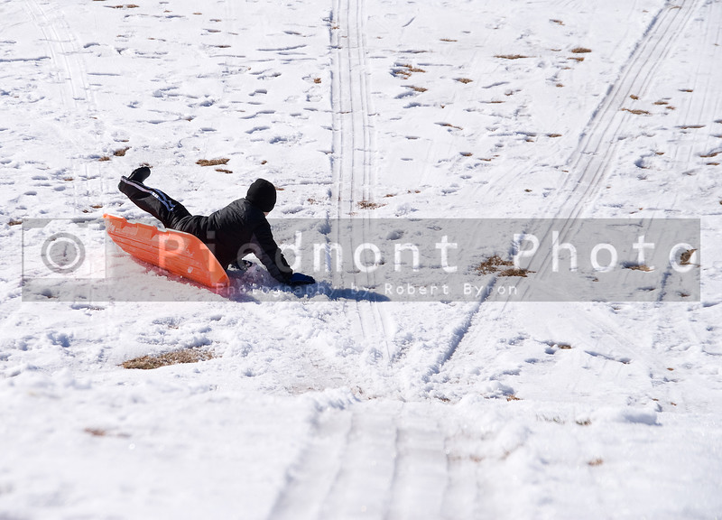 A young boy tumbling off of his sled.