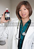 An Asian woman doctor holding a bottle of prescription medication