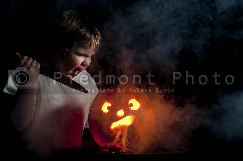 A crazy young boy carving a jack-o-lantern