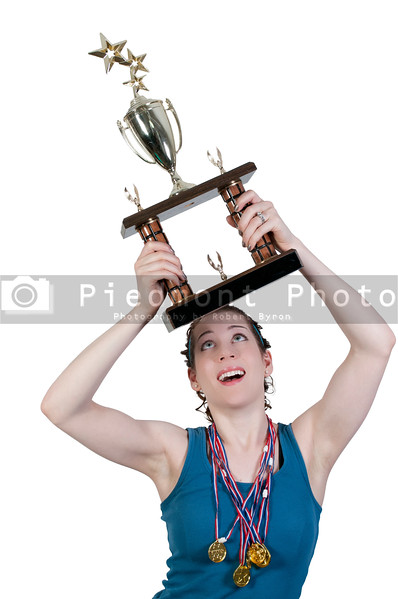 A beautiful woman wearing medals holding a large trophy
