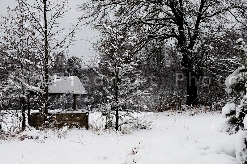 An old drinking well covered in snow from a blizzard