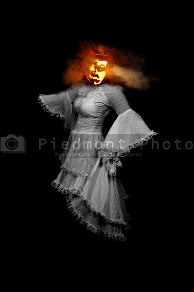 A Jack-O-Lantern headed woman floating in the dark.