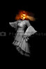 A Jack-O-Lantern headed woman floating in the dark.