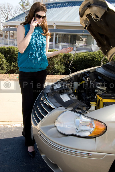 A beautiful young woman having car trouble