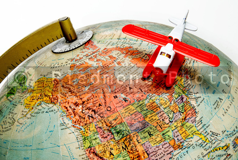 A toy airplane flying above a globe