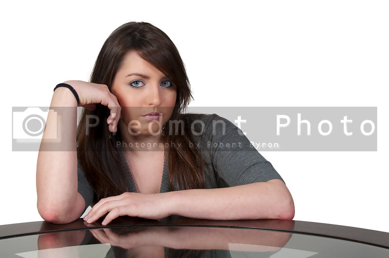 A beautiful young woman with pensive look sitting at a table