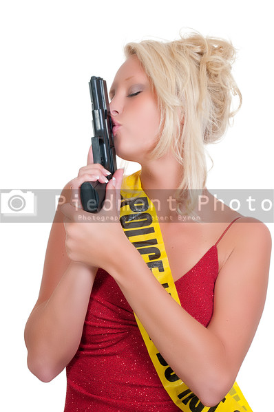 A beautiful police detective woman on the job kissing her gun