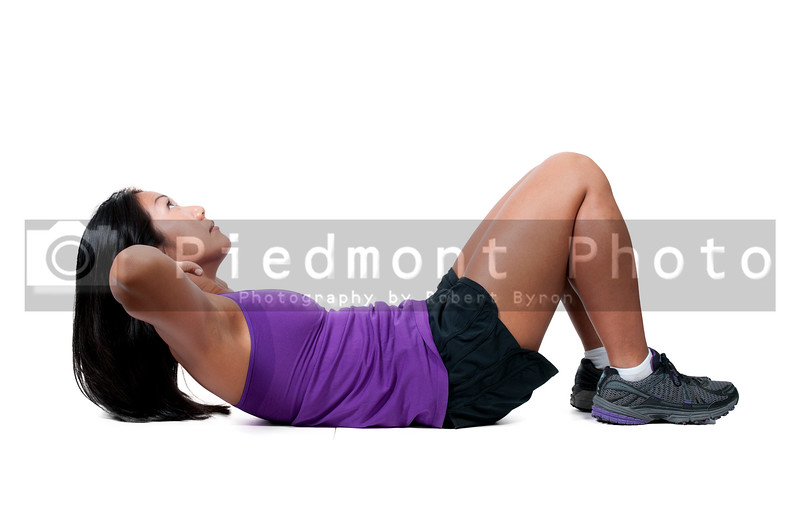 A beautiful young Asian woman exercising by doing crunches