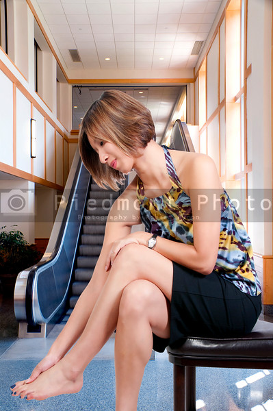 A beautiful young Asian business woman rubbing her sore tired feet