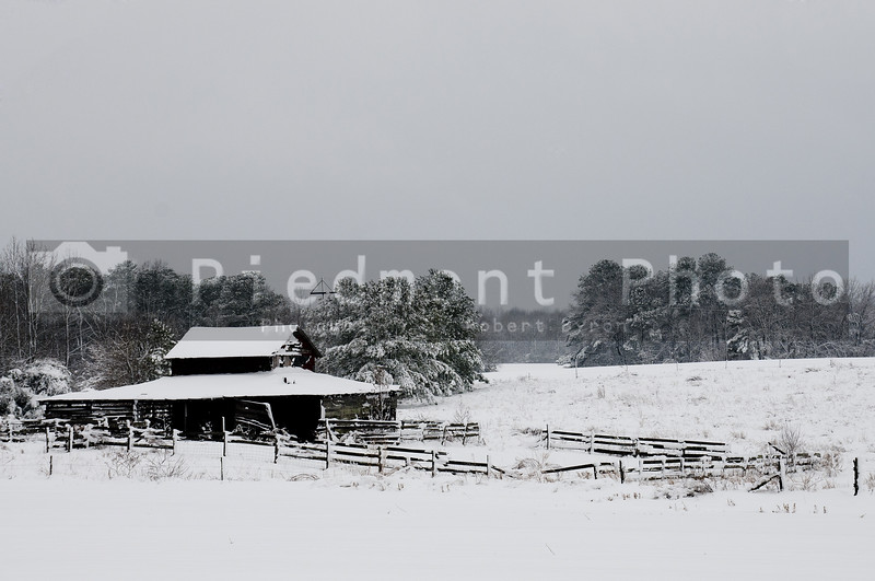 An old abandoned horse stable covered in a winter blizzard snow storm