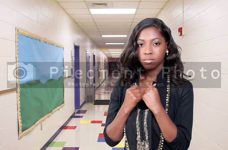 An african american woman teenager student or teacher in an elementary school hallway