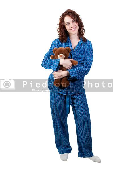A beautiful young woman wearing pajamas hugging her stuffed teddy bear