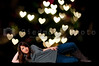 A young Beautiful Woman with a lovely smile in front of Valentine heart lights