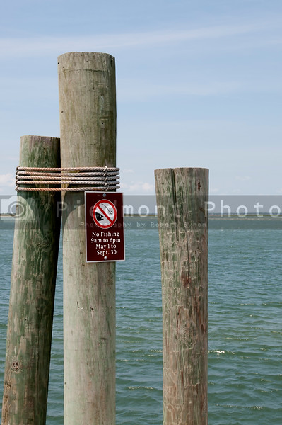 A no fishing sign on a dock at the ocean