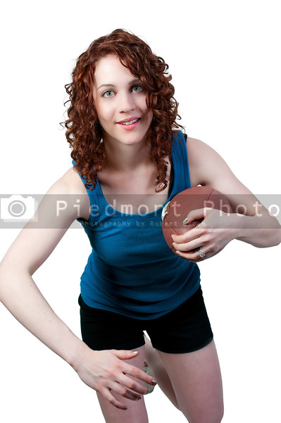 beautiful young woman playing a game of football running with the ball