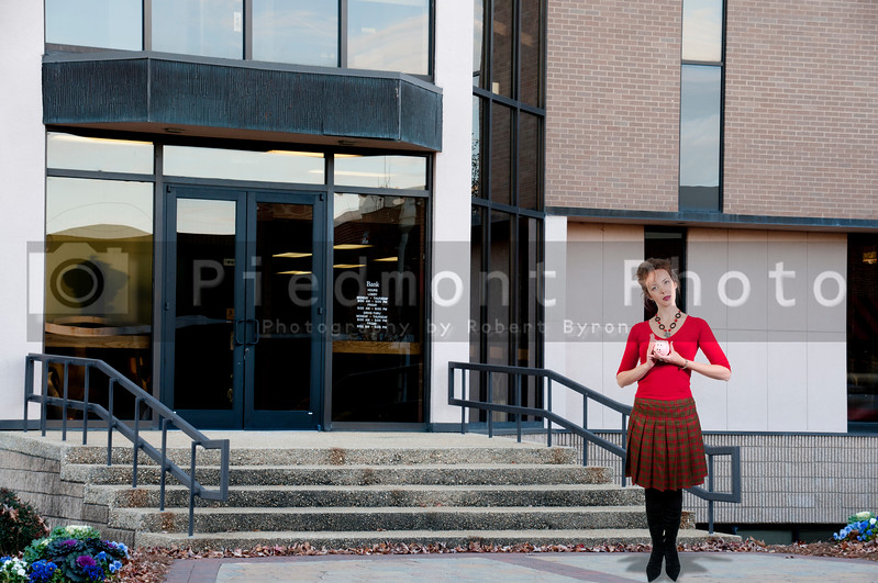 A beautiful woman standing in front of a bank while holding a piggy bank full of money she has saved