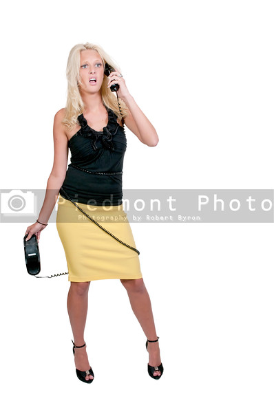 A beautiful woman talking on a phone tangled up in the cord
