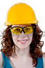 A Female Construction Worker wearing a hard hat and safety glasses