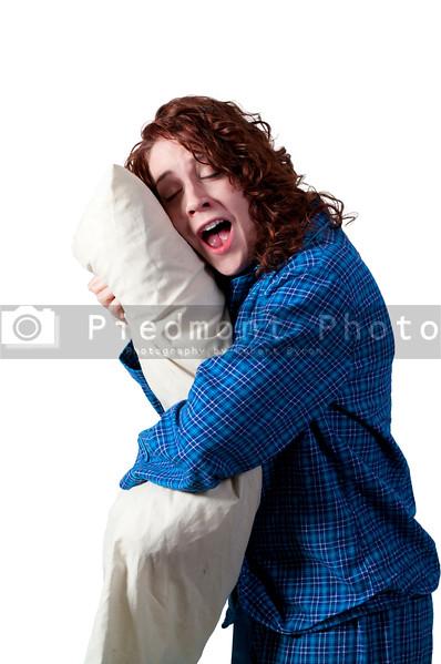A beautiful yawning young woman wearing pajamas hugging her pillow