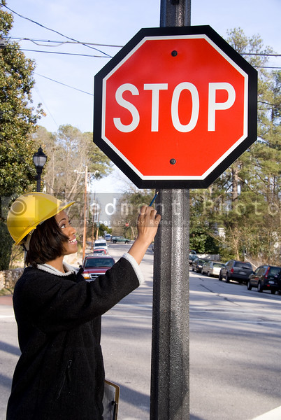 A Female Construction Worker inspecting a stop sign