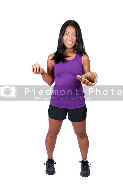 A beautiful Asian woman catching a baseball at a ball field